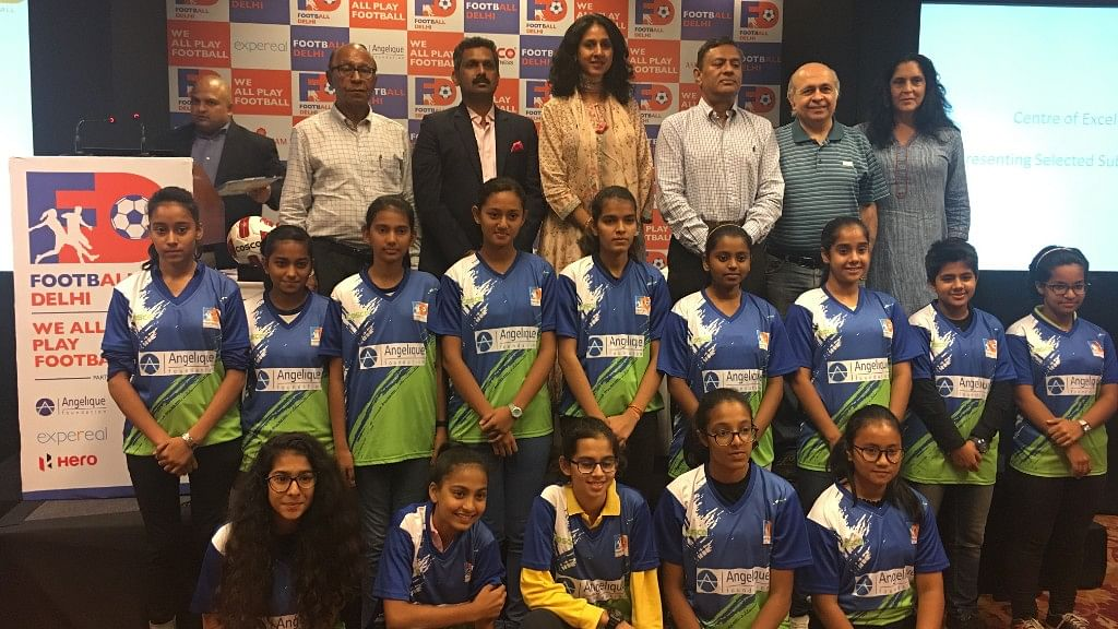 The group of Under-16 girls posing with the football officials.
