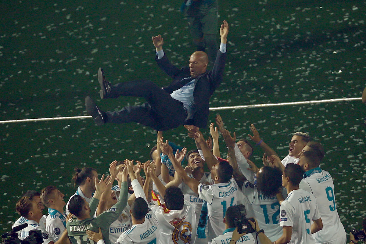 Real Madrid players lift head coach Zinedine Zidane into the air as they celebrate after winning the Champions League final at the Santiago Bernabeu stadium in Madrid.