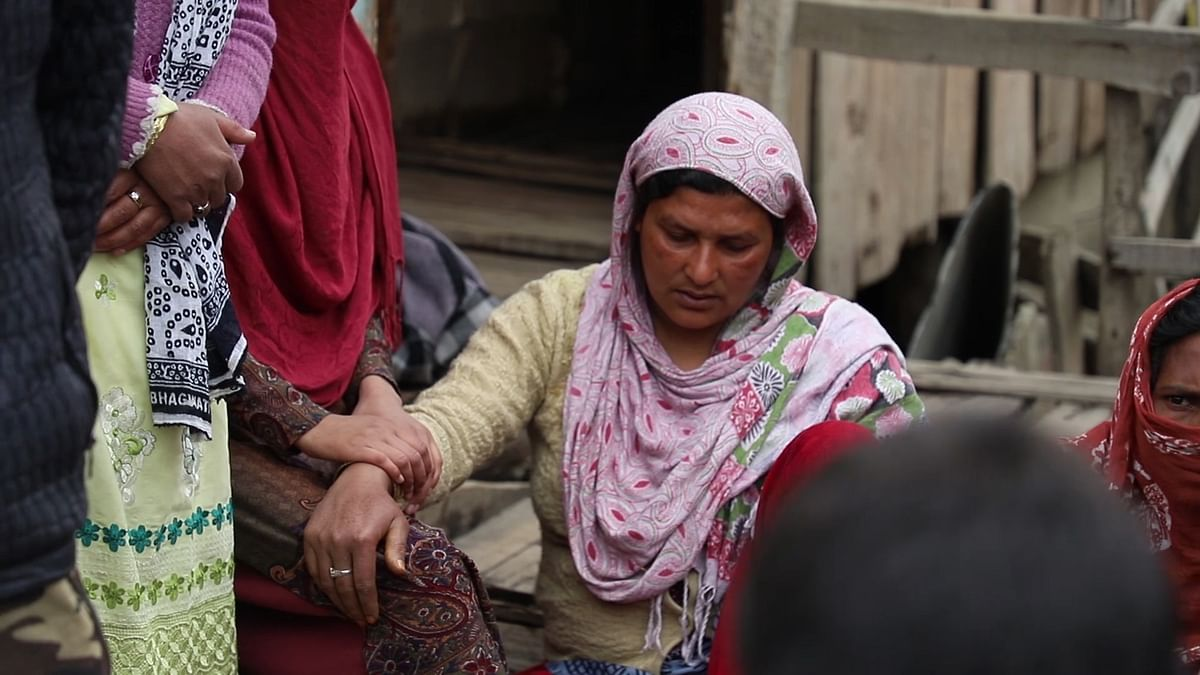 Relatives and neighbours comfort Adil's mother outside their house in Gasi Mohalla in Srinagar.