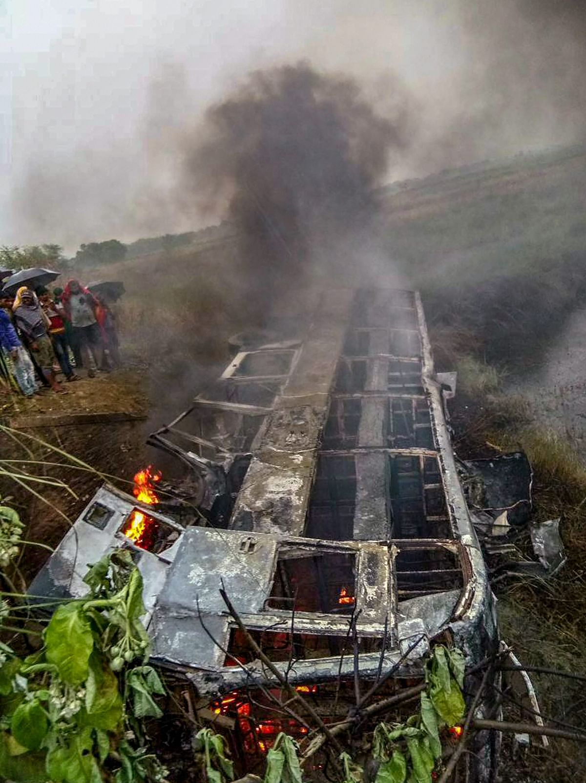 People watch the passenger bus which caught fire claiming two lives in Motihari district of Bihar on Thursday, 3 May.