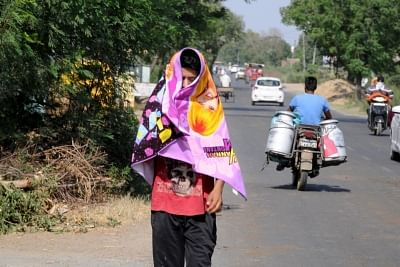 Amritsar: A man covers himself to avoid scorching sun on a hot day in Amritsar. (Photo: IANS)