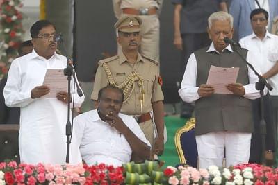 Bengaluru: Bengaluru: Karnataka Governor Vajubhai Vala administers the oath of office to Congress leader G. Parameshwara, during a swearing-in ceremony at Vidhana Soudha in Bengaluru on May 23, 2018. Parameshwara took oath as the Deputy Chief Minister of Karnataka. (Photo: IANS)