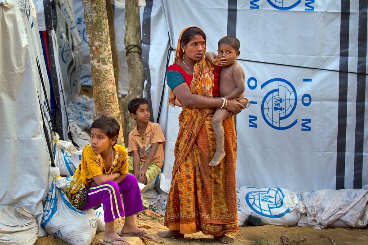 In this 16 January 2018, file photo, a Hindu refugee stands outside her makeshift shelter with her children, near Kutupalong refugee camp near Cox's Bazaar, Bangladesh.