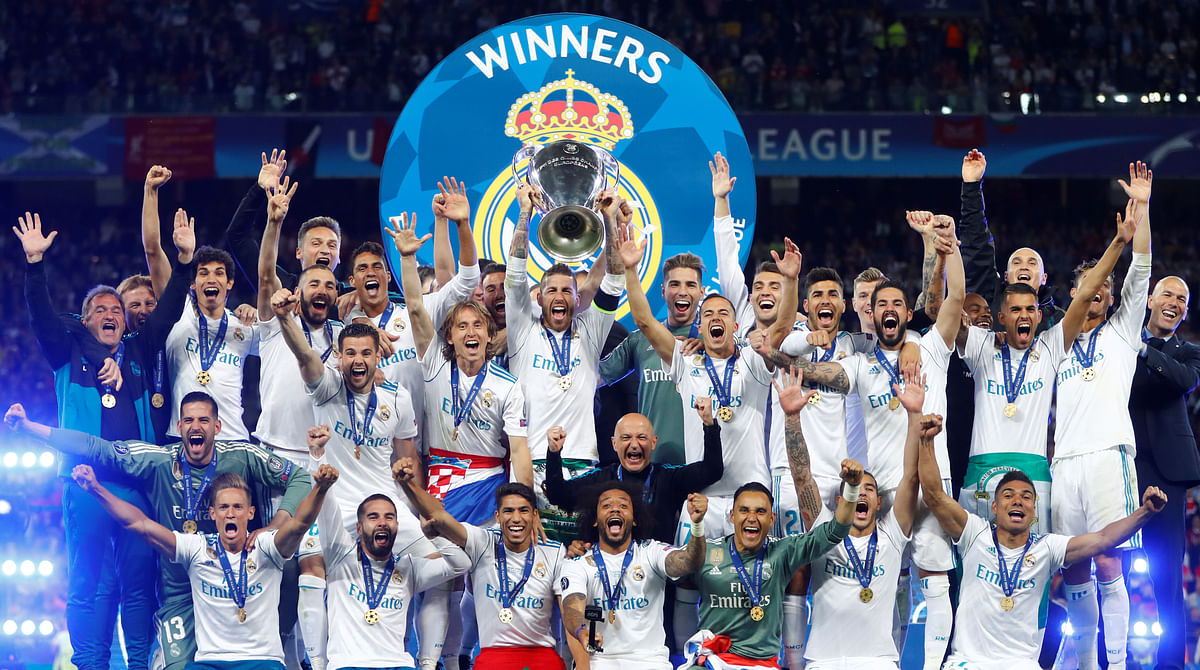 Real Madrid celebrate winning the Champions League with the trophy.