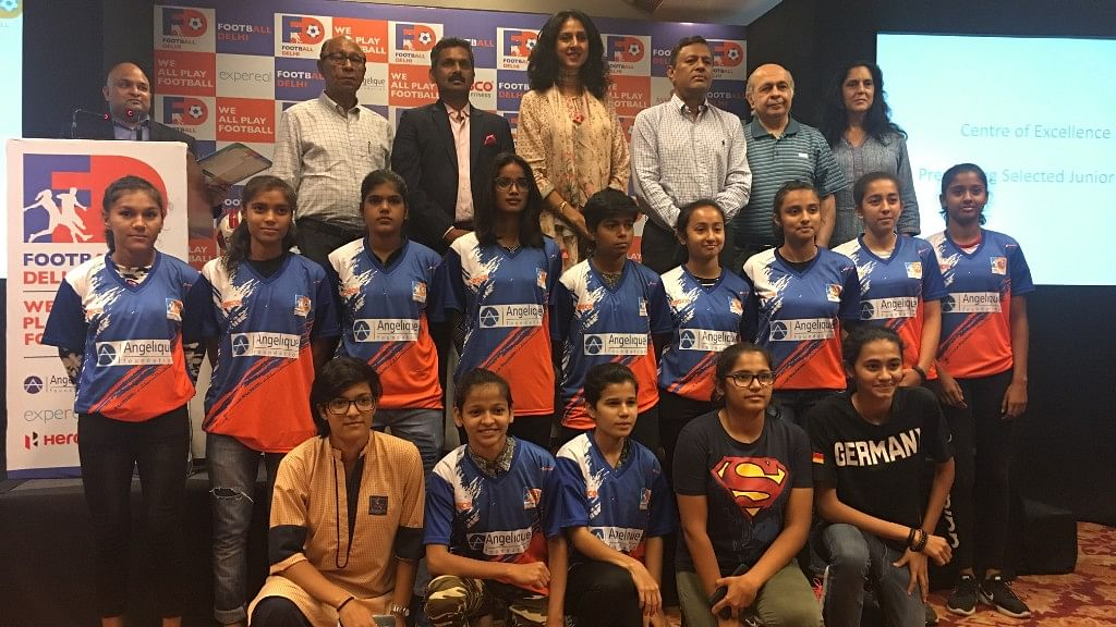 The group of Under-19 girls posing with the football officials.