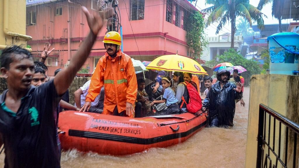 Rescuers shift people to a safer place from a flooded locality, after a thunderstorm, in Mangaluru.