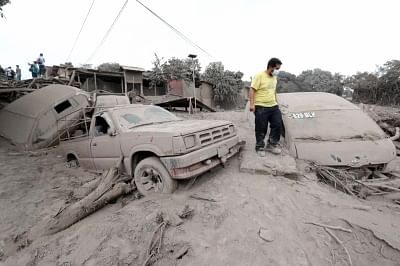 SAN MIGUEL LOS LOTES, June 5, 2018 (Xinhua) -- A man stands by damaged vehicles covered by ash in San Miguel Los Lotes, a village in Escuintla, Guatemala, on June 4, 2018. The death toll from the eruption of a highly active volcano near Guatemala
