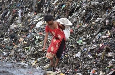 Guwahati : A rag picker seen looking for recyclable items in heaps of garbage at a dump-yard in Guwahati on the eve of World Environment Day, on June 4, 2018. (Photo: IANS)