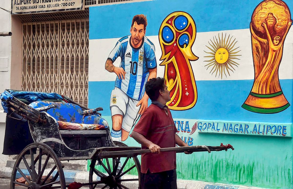 A hand-rickshaw puller moves past a wall painted with graffiti of Argentine footballer Lionel Messi ahead of FIFA World Cup 2018 in Kolkata on Sunday.