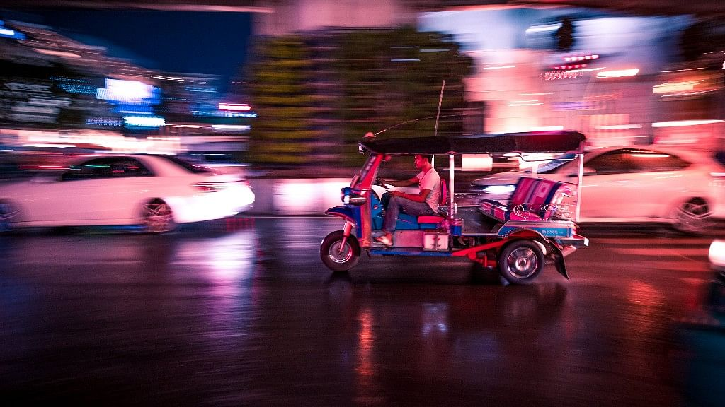 A tuktuk rushing past traffic as the signal turned green.