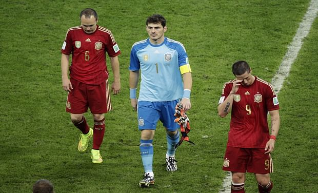 Spain's Andres Iniesta, goalkeeper Iker Casillas and Fernando Torres leave the pitch after the loss against Chile.