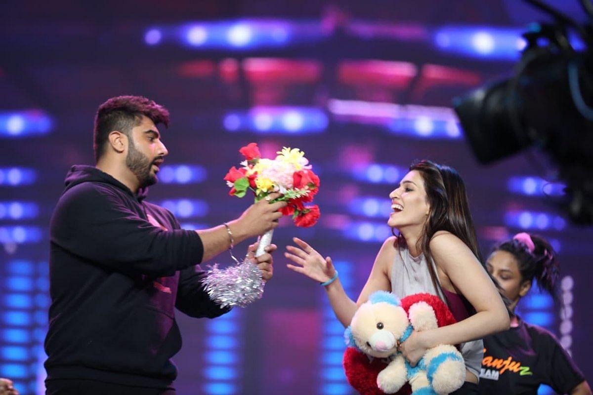 Arjun presents Kriti with flowers and a teddy bear.
