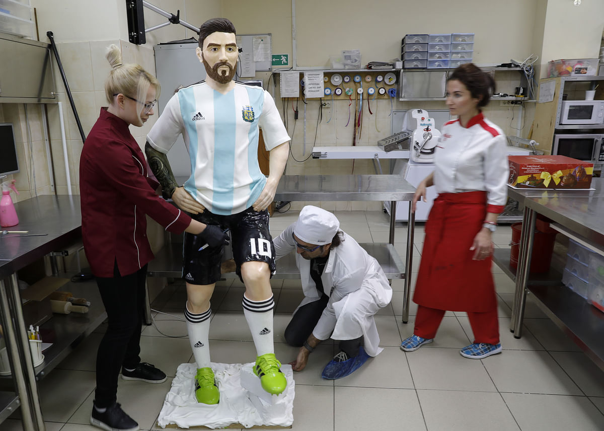 Confectioners working on the chocolate sculpture of Lionel Messi.