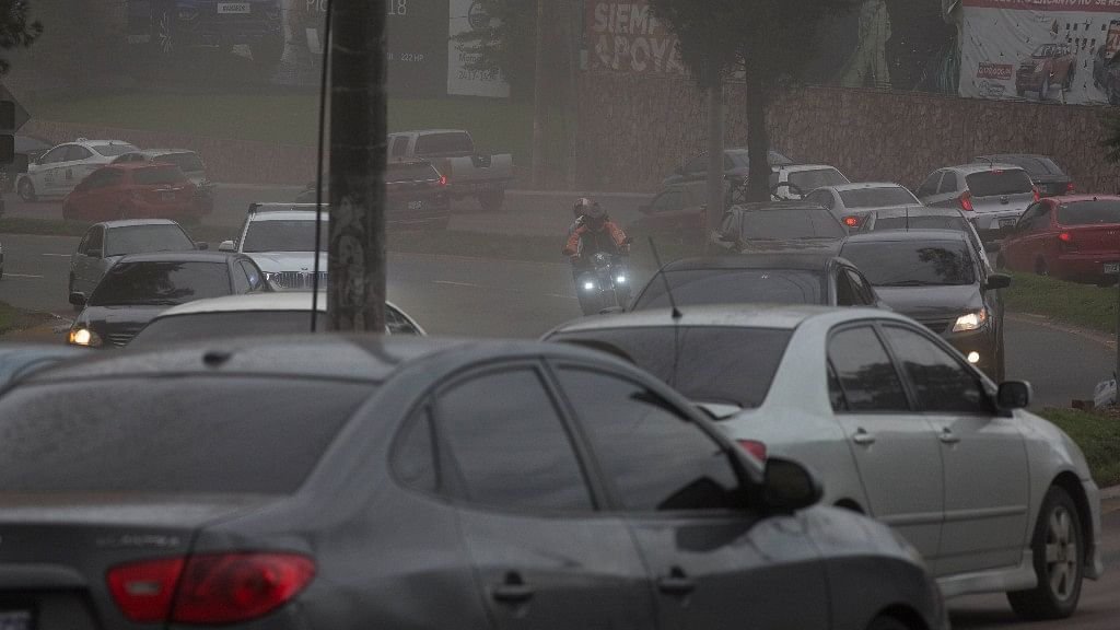 Drivers make their way through a light rain of volcanic ash, as the Volcan de Fuego erupts, in Guatemala City on Sunday, 3 June.