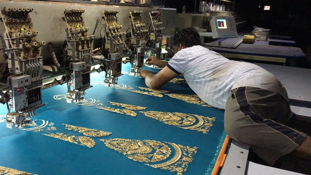 An embroidery worker threads the jari into the needle