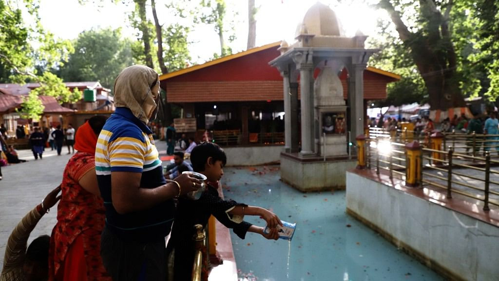 A little devotee offers milk to the Goddess as part of the ritual during Kheer Bhawani festival.