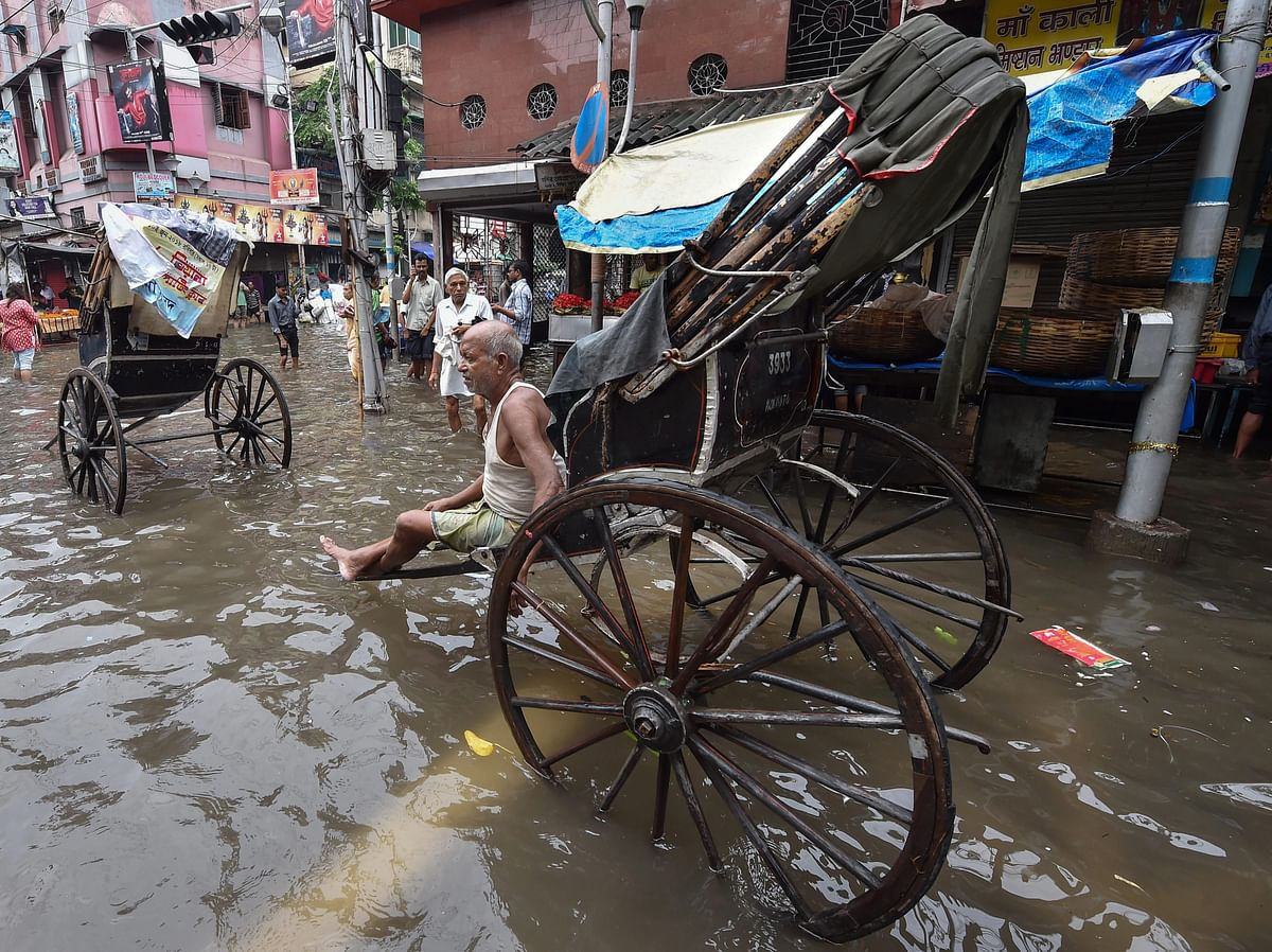 A rickshaw puller waits for passengers on a water-logged street after heavy rainfall, in Kolkata on Tuesday, June 26, 2018