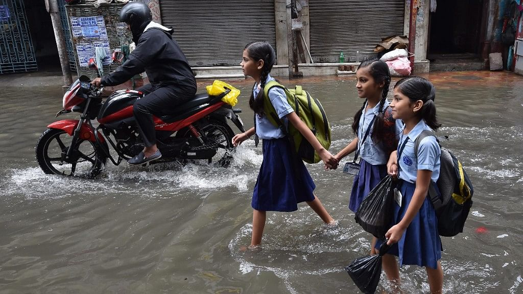 Students wade through a water-logged street after heavy rainfall  in Kolkata on 26 June 2018.