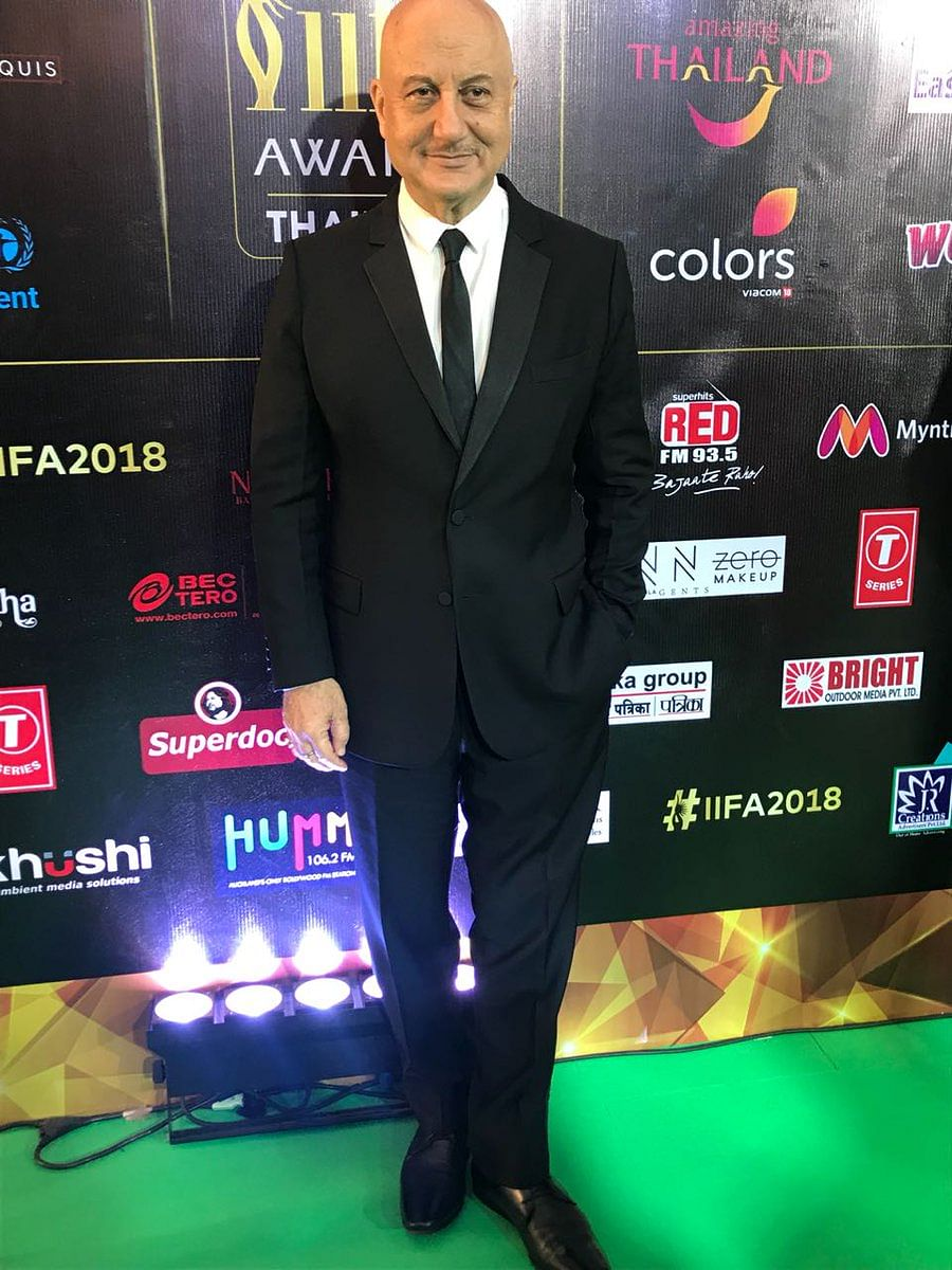 Anupam Kher keeps it simple in a  black suit and a slim tie.