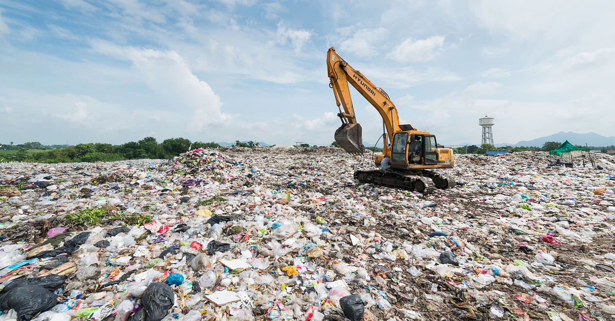 A Backhoe car works in a sanitary landfill site.