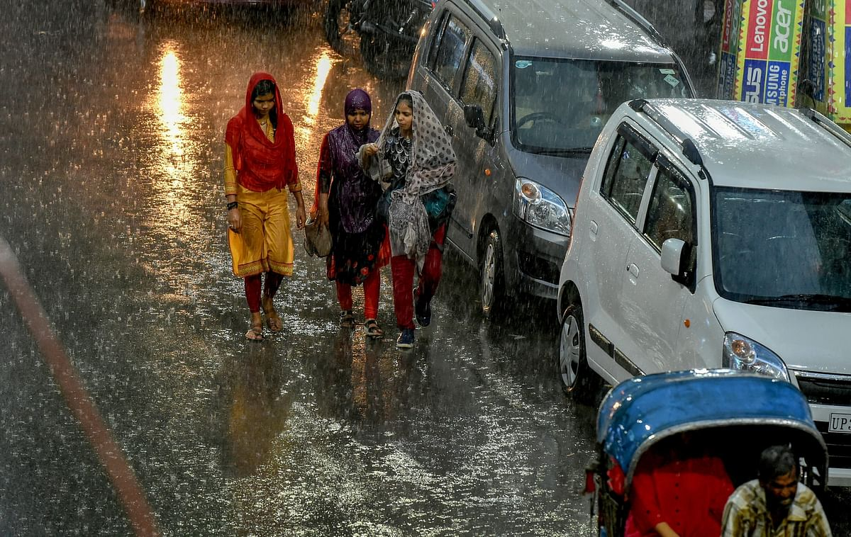 Pedestrians try to make their way across a street during heavy rain, in Lucknow on Tuesday, June 26, 2018.