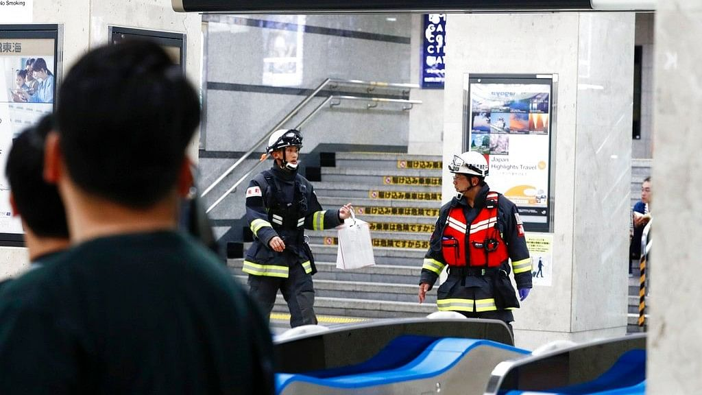 Firefighters are seen at Odawara station as a Japan's bullet train made an unscheduled stop due to a knifing attack in Odawara, Japan, late Saturday, June 9, 2018.
