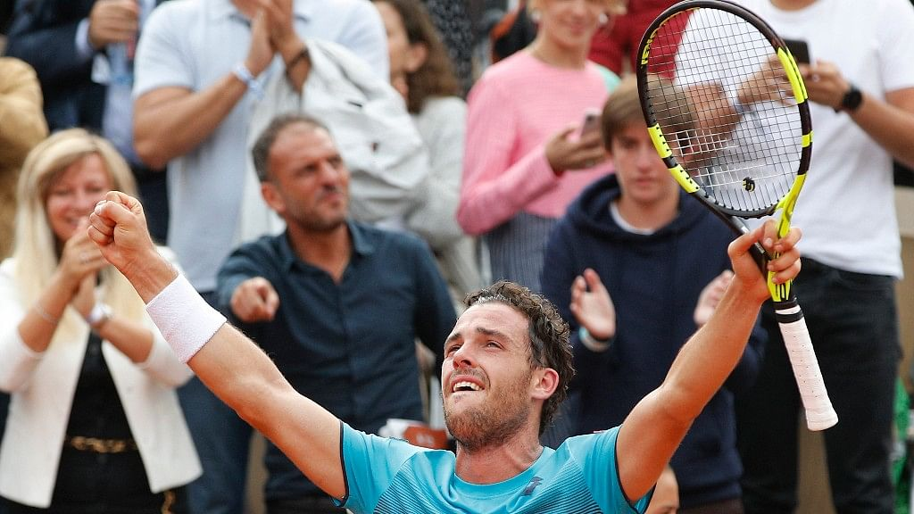 Italy's Marco Cecchinato celebrates after winning his quarterfinal match in the French Open against Novak Djokovic in four sets 6-3, 7-6 (7-4), 1-6, 7-6 (13-11) at the Roland Garros  in Paris on Tuesday.