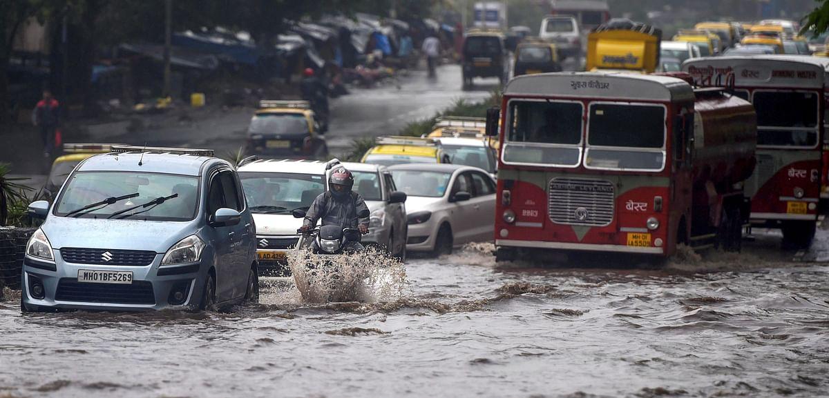 Vehicles wade through water-logged tracks during heavy rains, in Mumbai on Monday, June 25, 2018.