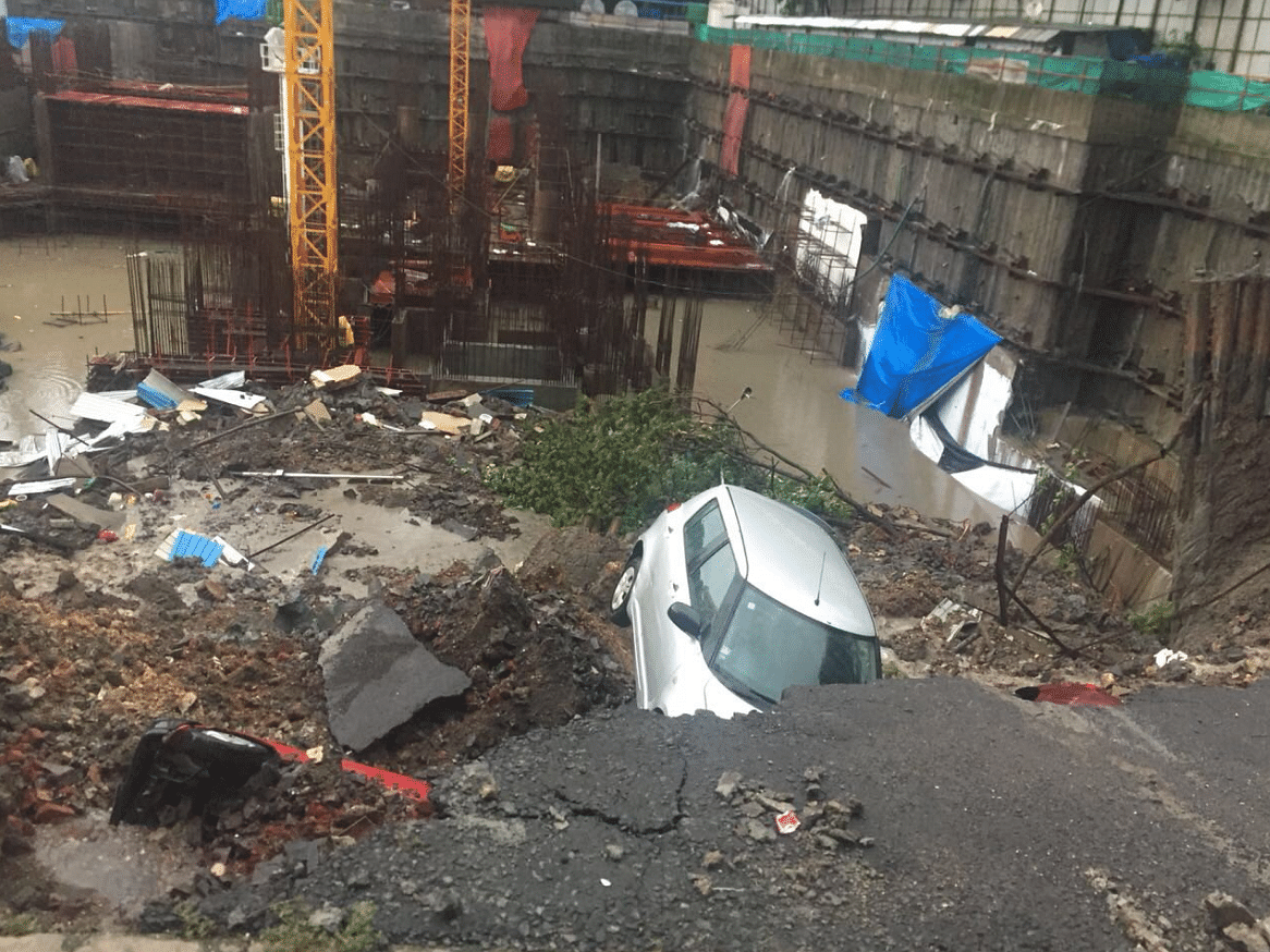 Cars buried under rubble after a wall caved in following heavy rains in Mumbai.