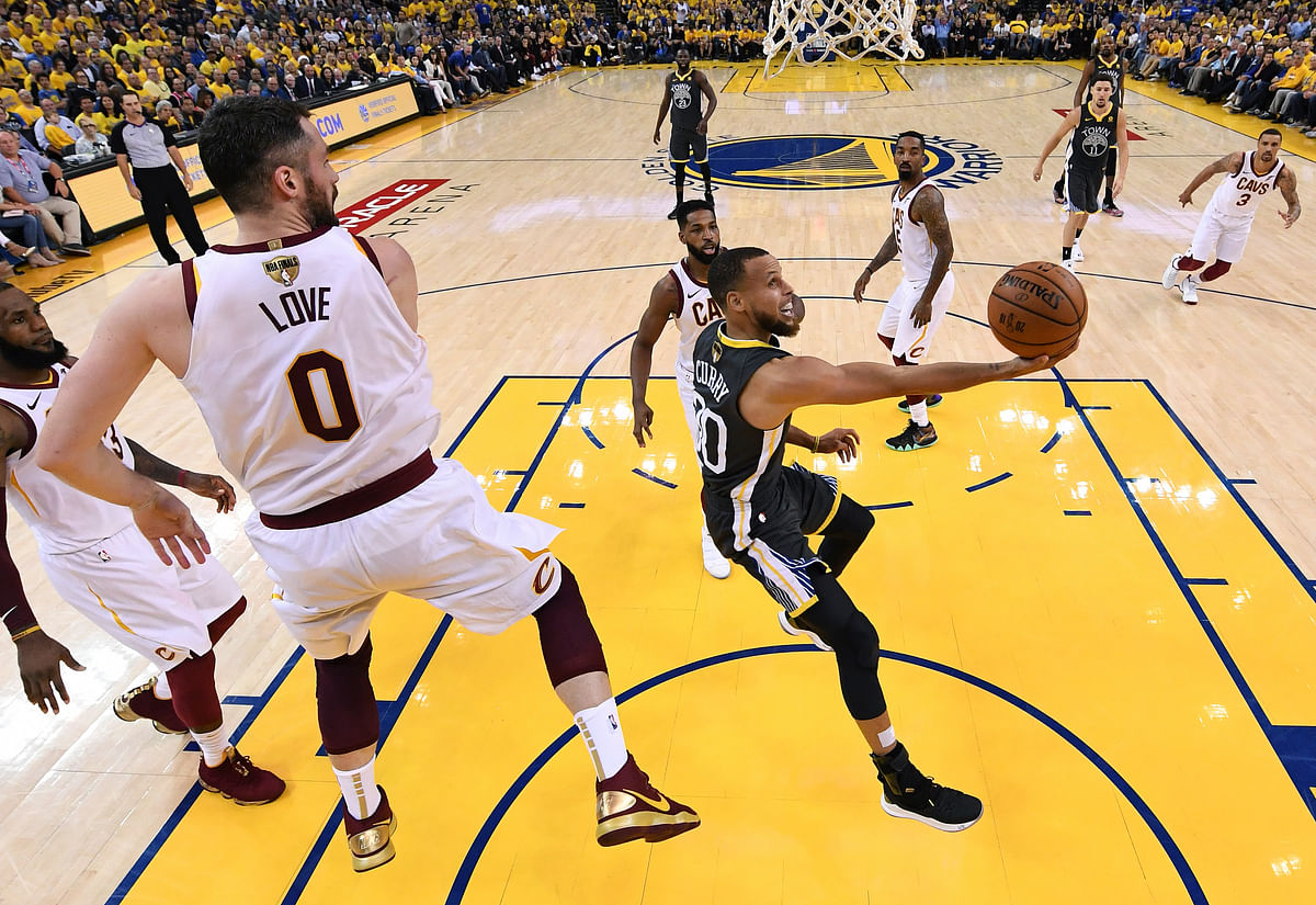 Golden State Warriors guard Stephen Curry, right, shoots against Cleveland Cavaliers forward Kevin Love (0) during the first half of Game 2 of basketball's NBA Finals.