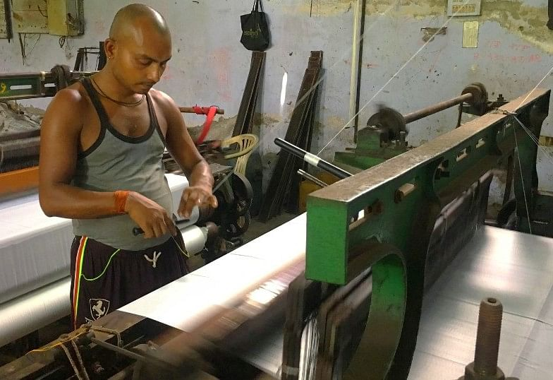 A part time worker at a power loom unit does his job.