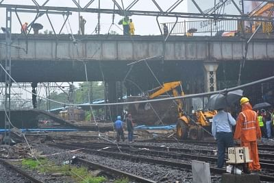Mumbai: Rescue workers clear the debris after a portion of the Gokhale footover Bridge, running east-west over the Andheri station crashed over the Western Railway (WR) tracks injuring at least three, at Andheri in Mumbai on July 3, 2018. Coupled with torrential overnight rains, the crash severely hit Mumbai