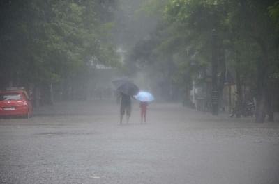 Mumbasi: People shield themselves with umbrellas as heavy rains lash Mumbai, on July 10, 2018. (Photo: IANS)