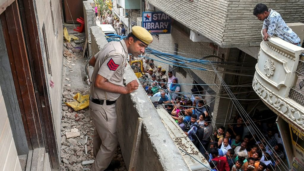 A policeman stands in the balcony of the house, where 11 members of a family were found dead  in Burari area of Delhi on 1 July.
