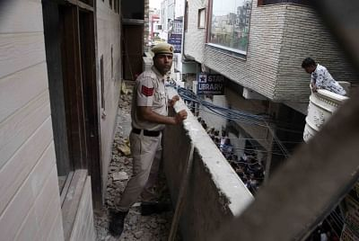New Delhi: A police personnel carries out investigation at the site where 11 members of a family were found dead -- some blindfolded and hanging from an iron grill ceiling -- at their home, in New Delhi on July 1, 2018. According to Joint Commissioner of Police Rajesh Khurana, while some bodies of them were found hanging from an iron grill ceiling (used as a ventilator) in the courtyard while others were lying on the floor blindfolded with their hands and legs tied at their two-storey house in S