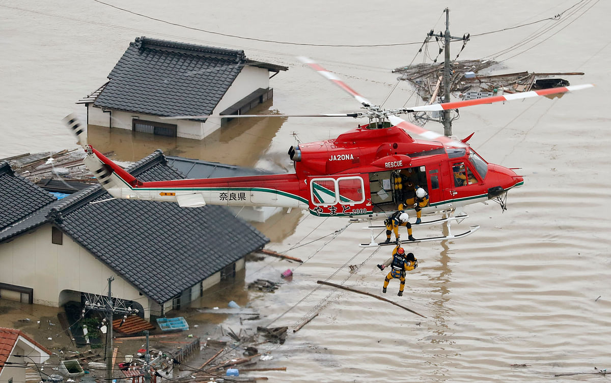 A resident is rescued in a flooded area in Kurashiki, Okayama prefecture, following heavy rain.