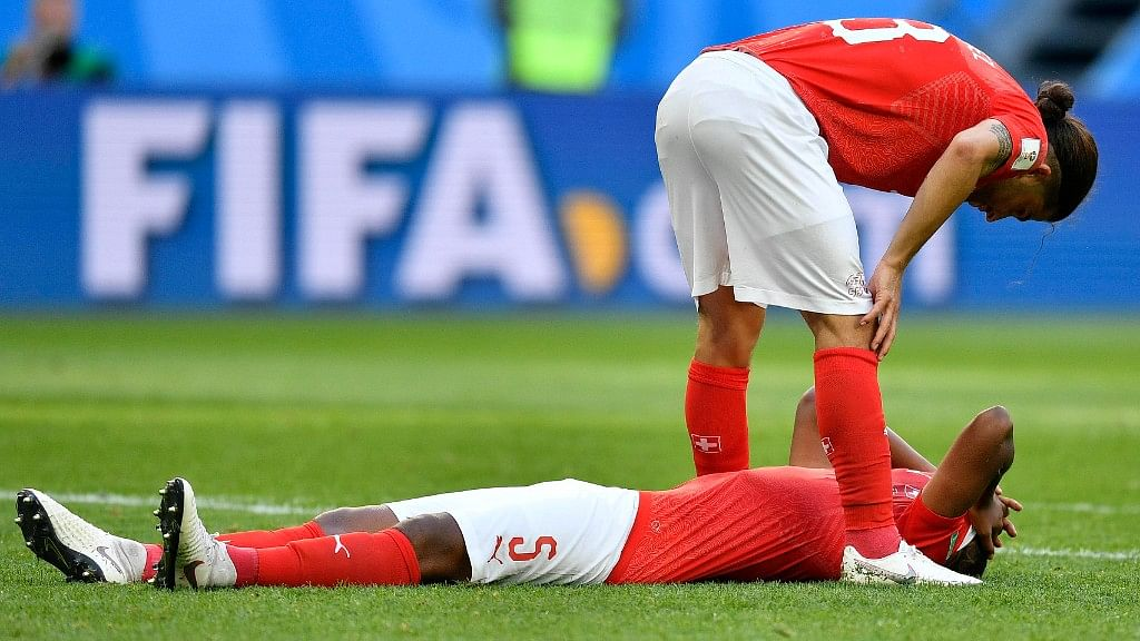 Switzerland's Ricardo Rodriguez (top) and Switzerland's Manuel Akanji react after their team lost their Round of 16 match against Sweden at the St. Petersburg Stadium on Tuesday.
