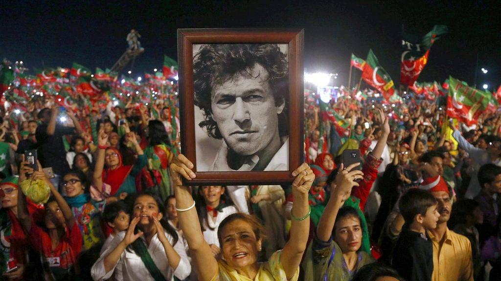 In this 22 July 2018, file photo, a woman supporter of Tehreek-e-Insaf party raises a picture of her party's leader Imran Khan during an election campaign rally in Karachi, Pakistan.