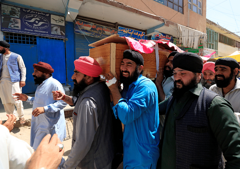 Relatives carry the dead body of the a victim of the blasts on 3 July.