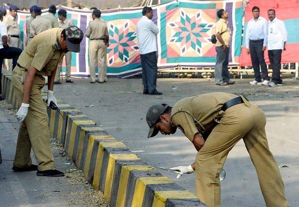 Policemen inspecting the scene after the 2010 Chinnaswamy stadium blast.