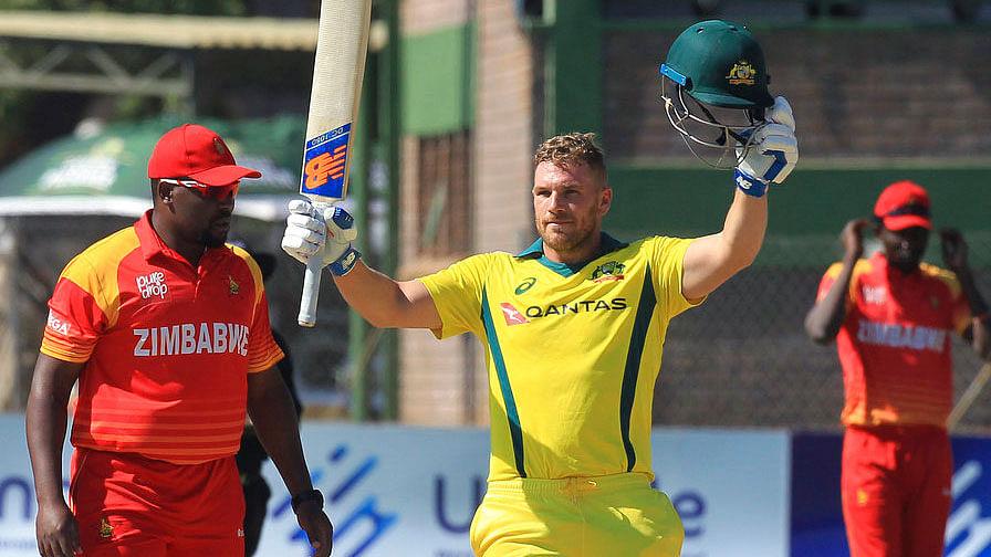Aaron Finch celebrates after scoring a century against Zimbabwe.