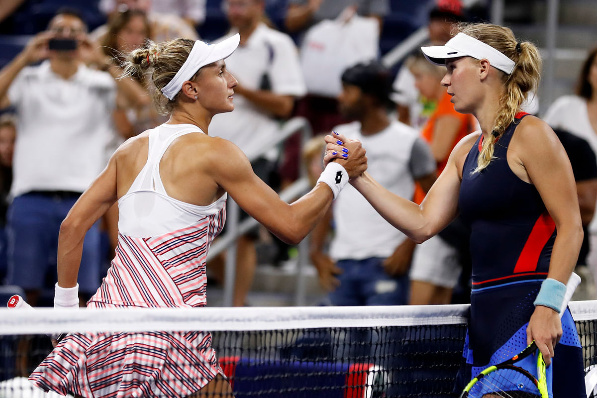 Lesla Tsurenko, left, of Ukraine, shakes hands with Caroline Wozniacki, of Denmark, after their match during the second round of the U.S. Open tennis tournament, Thursday, Aug. 30, 2018.