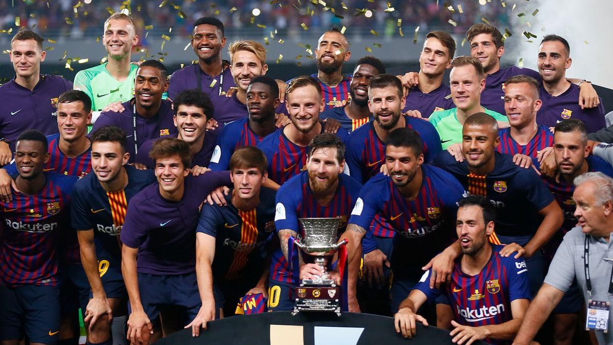 Barcelona players pose with the trophy after winning the Spanish Super Cup soccer match between Sevilla and Barcelona in Tangier, Morocco, Sunday, Aug. 12, 2018. Barcelona won 2-1.