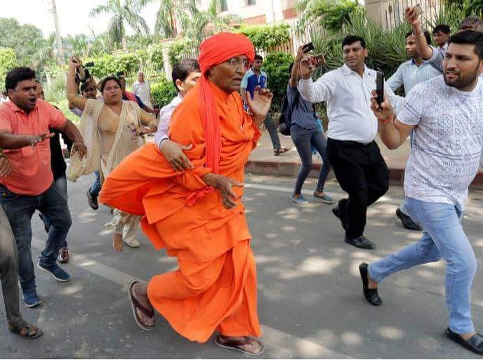Swami Agnivesh being attacked by BJP workers outside party's office in Delhi on 17 August 2018.