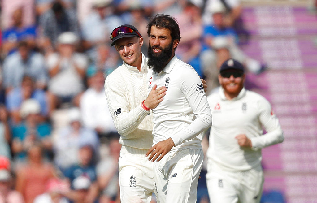 Moeen Ali celebrates a wicket with his teammates.