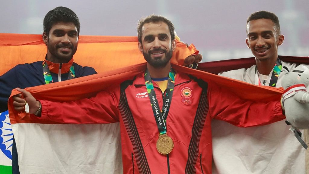 Manjit Singh (centre) stands with silver medalist and compatriot India's Jinson Johnson (left) and bronze medalist Qatar's Abubaker Abdalla on the podium at the 18th Asian Games on Tuesday.