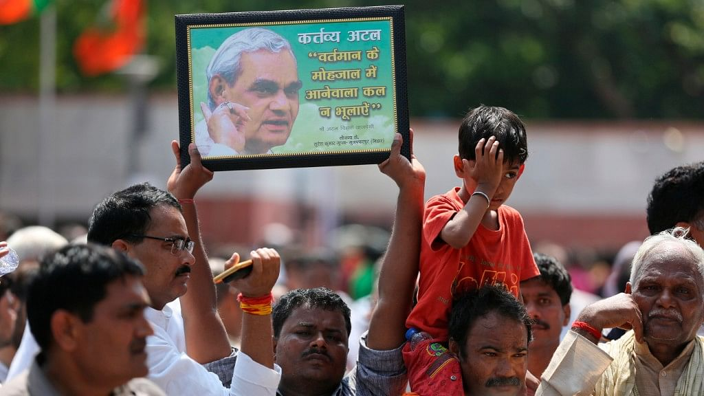 A mourner holds a portrait of former Indian Prime Minister Atal Bihari Vajpayee as he stands with others outside the BJP headquarters on 17 August.