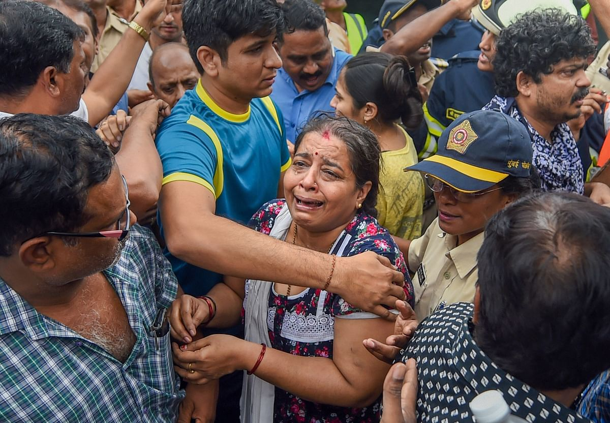 A woman breaks down after she was rescued from the Crystal Tower.