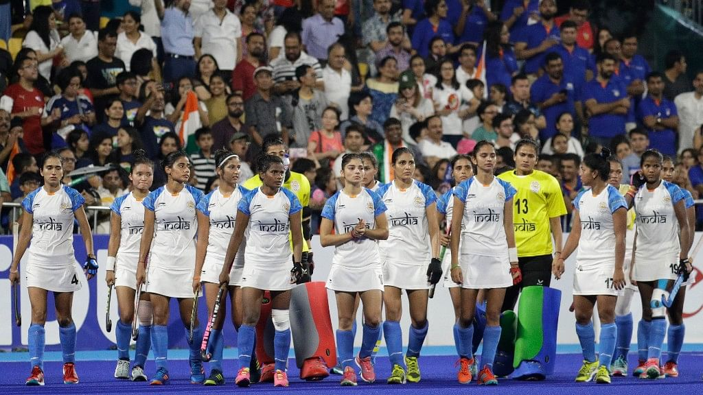 A dejected Indian women's hockey team walks after losing to Japan.
