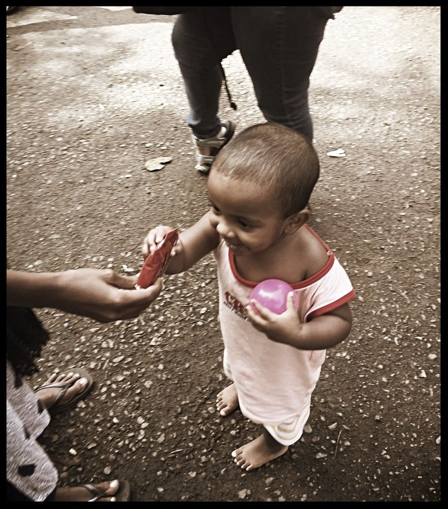 Two-year-old Amaya taking a chocolate from his mother Sunita.
